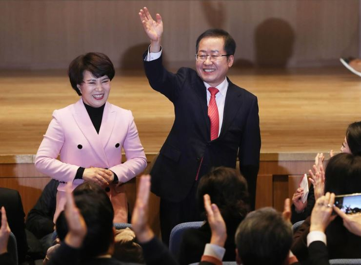 Hong Joon-pyo, right, the former main opposition Liberty Korea Party leader, waves before holding a publication event to promote his new book at The-K Twin Towers in Seoul, Wednesday. He declared his candidacy for the party leadership to hold the Moon Jae-in administration in check. / Yonhap