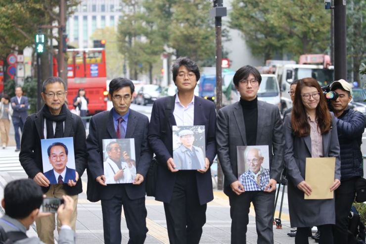 Japanese and Korean civic activists and lawyers visit Nippon Steel & Sumitomo Metal headquarters in Tokyo, holding pictures of deceased wartime forced laborers, Nov. 12, calling for a speedy compensation in line with the top Korean court's ruling. / Yonhap
