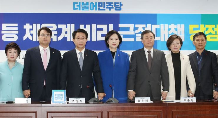 Education Minister Yoo Eun-hae, center, Culture Minister Do Jong-hwan, third from right, Gender Equality and Family Minister Jin Sun-mee, second from right and Rep. An Min-suk of the ruling Democratic Party of Korea (DPK) hold hands at a meeting between the government and the DPK at the National Assembly, Thursday, to come up with measures to eradicate sexual assault in sports. / Yonhap