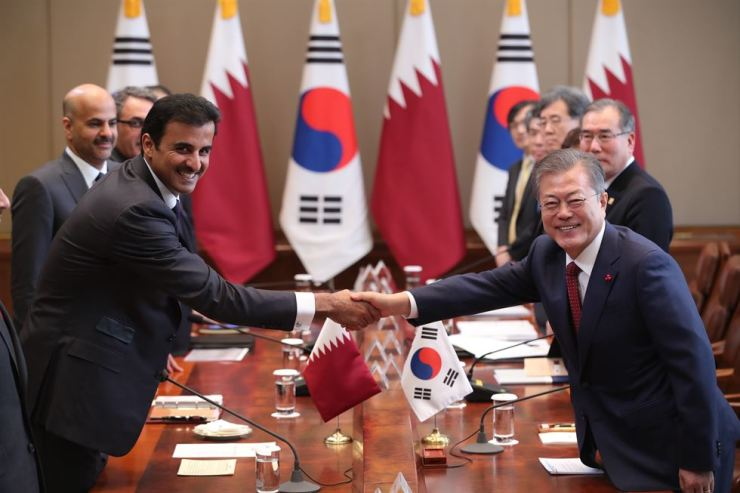 President Moon Jae-in, right, shakes hands with Emir Sheikh Tamim bin Hamad Al Thani, left, Qatar's head of state, at the start of their summit at Cheong Wa Dae, Monday. Yonhap