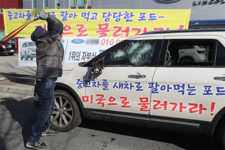 The owner of a Ford Explorer smashes his car with a baseball bat in Jeonju, North Jeolla Province, Jan. 20. Yonhap