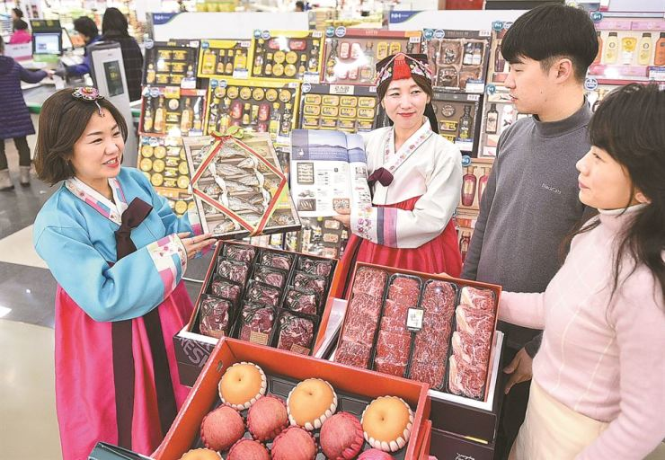 Nonghyup Hanaro Mart employees in Korean dress show customers gift sets for the upcoming Lunar New Year at the store, Friday. The discount chain said it will carry out various promotional events, including sales of gift sets offering domestic agricultural products, at its stores nationwide from Jan. 21 to Feb. 4. / Courtesy of Nonghyup Hanaro Mart