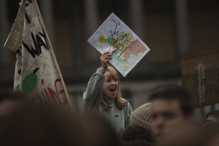 A young woman holds a map of Europe that reads: 'Wake up!' during a protest against climate change in Brussels, Jan. 10. The demonstration attracted many young people to protest on green issues. AP