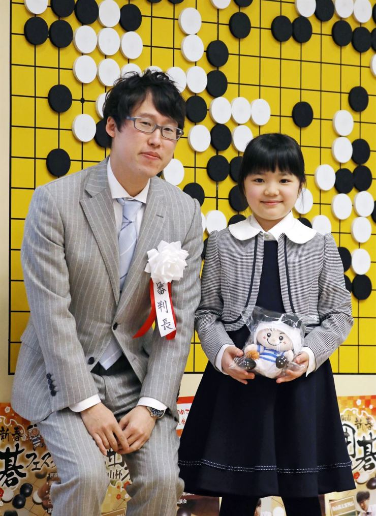 Sumire Nakamura, right, poses with go board game player Yuta Iyama in Osaka, western Japan, Sunday. The Japanese schoolgirl, who trained in Seoul for about two years under the ninth-degree professional player Han Jong-jin, will be 10 when she becomes the youngest professional player as of April 1. / EPA-Yonhap
