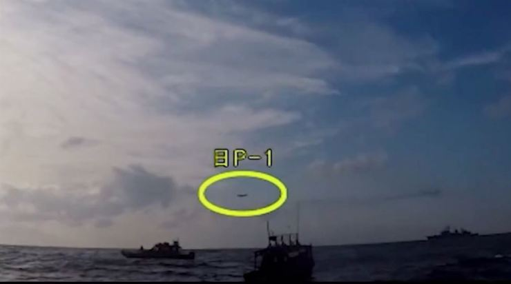 The captured image shows Japan's P-1 patrol plane, circled, and the South Korean warship Gwanggaeto the Great, below. / Captured from Youtube