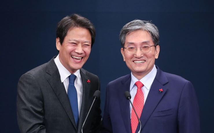 Former presidential chief of staff Im Jong-seok, left, smiles with his replacement Noh Young-min after announcing a changes to the senior presidential secretaries at Cheong Wa Dae, Tuesday. Yonhap