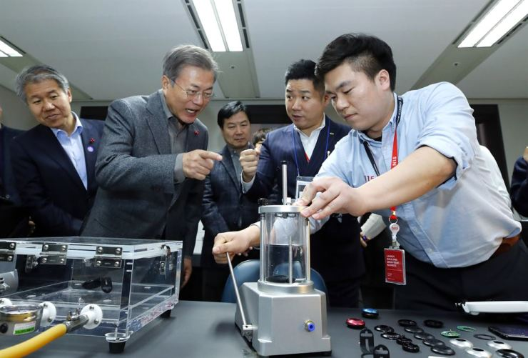 President Moon Jae-in listens to an explanation about a smartphone-linked scuba diving product produced by a Korean startup during a visit to the N15 industrial lab in Seoul, last week. Yonhap