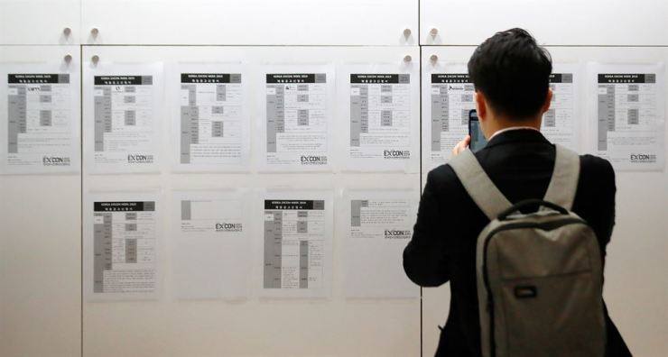 A young jobseeker takes a photo of a company recruitment notice at a job convention in COEX, Seoul, Wednesday. Yonhap