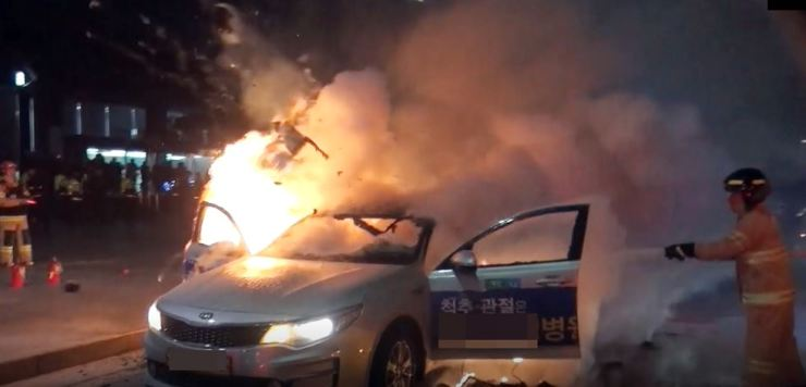 Firefighters put out a fire in a taxi near Gwanghwamun Station in central Seoul, Wednesday. The taxi driver set his car and himself on fire to protest the introduction of ridesharing services. The fire was contained within six minutes, but the driver died Thursday morning while being treated in hospital. / Yonhap