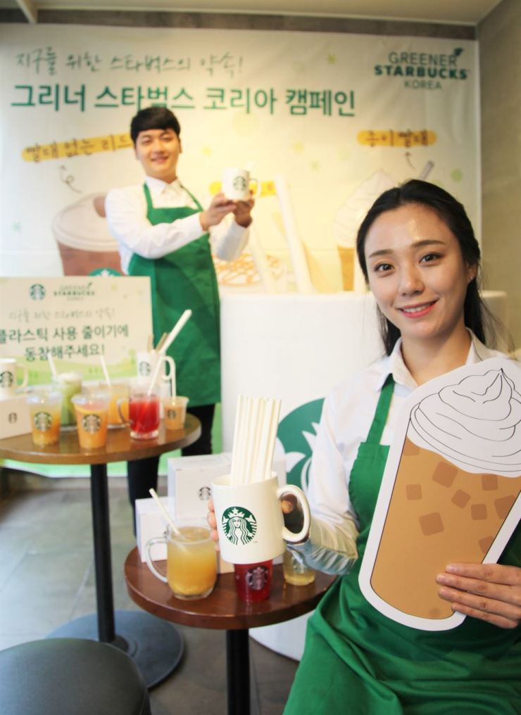 Starbucks Coffee Korea employees promote the coffeehouse's paper straws at a Starbucks store in Seoul in this November 2018 file photo. / Courtesy of Starbucks Coffee Korea