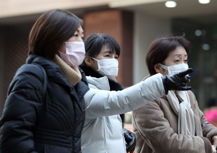 Masked foreign tourists walk down a street in Myeongdong, Seoul, Sunday, amid high levels of fine dust reported nationwide. / Yonhap
