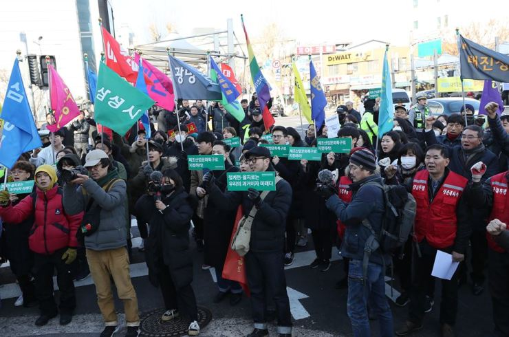 Dozens of store owners and artists stage a rally near Cheonggye Stream, Thursday, urging the Seoul Metropolitan Government to scrap its redevelopment plan in the Euljiro area of downtown Seoul. / Yonhap