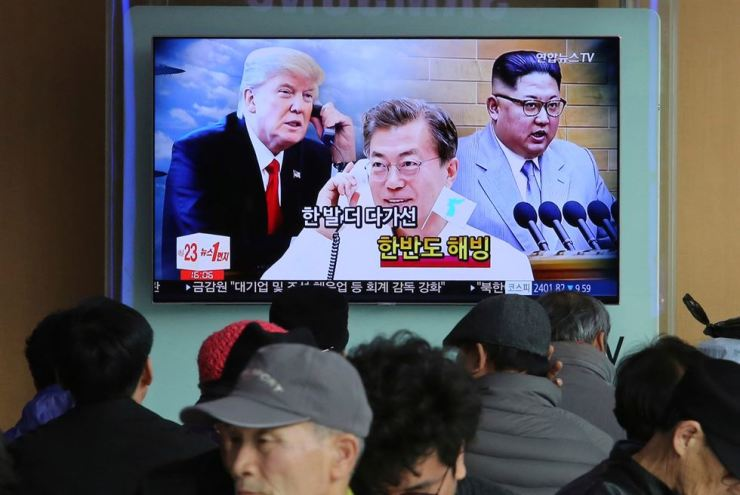 In this March 7, 2018, file photo, people watch a TV screen showing images of North Korean leader Kim Jong Un, right, South Korean President Moon Jae-in, center, and U.S. President Donald Trump at the Seoul Railway Station in Seoul, South Korea. AP-Yonhap