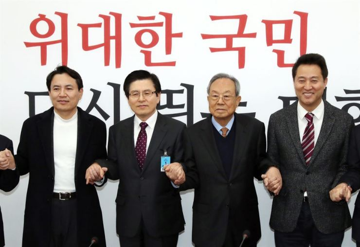 Contenders of the leadership race of the main opposition Liberty Korea Party (LKP) hold hands in a party meeting at the National Assembly, Wednesday. From left are, Rep. Kim Jin-tae, former Prime Minister Hwang Kyo-ahn, Park Kwan-yong, the chief of the party's election preparation panel and former Seoul Mayor Oh Se-hoon. / Yonhap