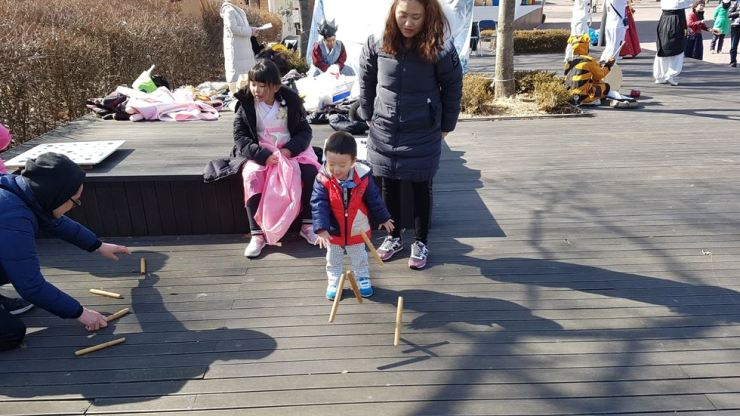 Families play a game with yut, wooden toy sticks, at Children's Grand Park / Courtesy of Seoul Metropolitan Government