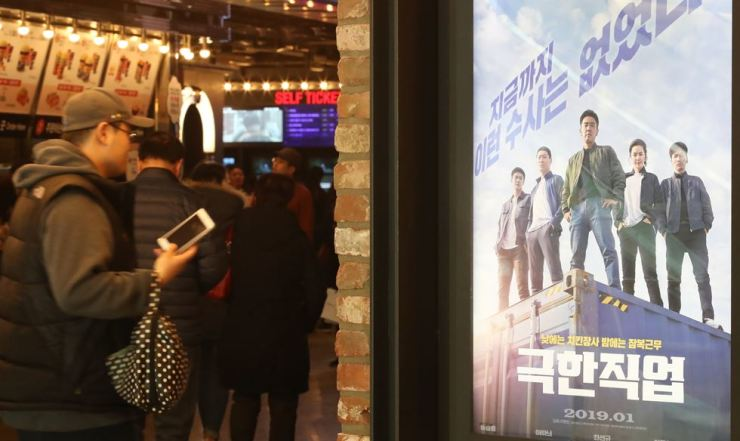 People wait for their movies at a theater in Seoul on Feb. 6. Yonhap