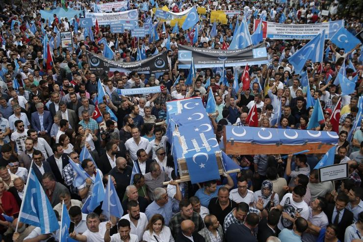 In this Saturday, July 4, 2015, file photo, Uighurs living in Turkey and their supporters, some carrying coffins representing Uighurs who died in China's far-western Xinjiang Uighur region, chant slogans as they stage a protest in Istanbul, against what they call as oppression by Chinese government to Muslim Uighurs in the province. AP