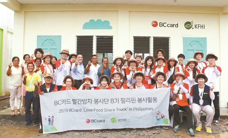 BC Card employees pose with locals after completing their overseas charity mission in Leyte, the Philippines, Feb. 17. The card firm's volunteers provided a food truck catering for Amandangay elementary school students in the region from Feb. 12 to 17. Courtesy of BC Card