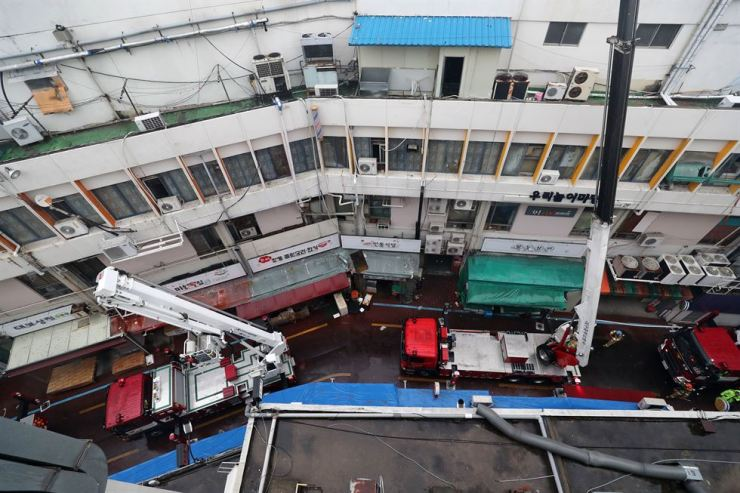 Fire authorities rescue people from fire at a sauna on the fourth floor of a seven-story building in Daegu, Tuesday. The fire killed two and injured about 50. / Yonhap