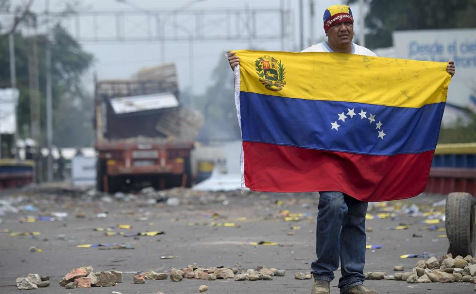 Demonstrators throw stones at a line of Venezuelan national guards at the border in Pacaraima, Brazil, Feb. 24. Reuters
