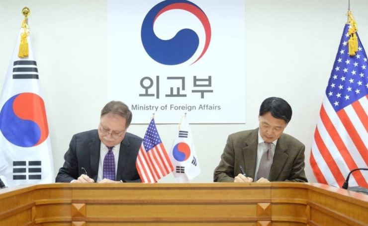 Chang Won-sam, Korea's top negotiator in defense cost sharing negotiations signs an agreement with his U.S. counterpart Timothy Betts, a deputy assistant secretary at the U.S. Department of State, after reaching a provisional consensus on the renewal of the Seoul-Washington Special Measures Agreement this year, at the headquarters of the Ministry of Foreign Affairs, Sunday. / Yonhap