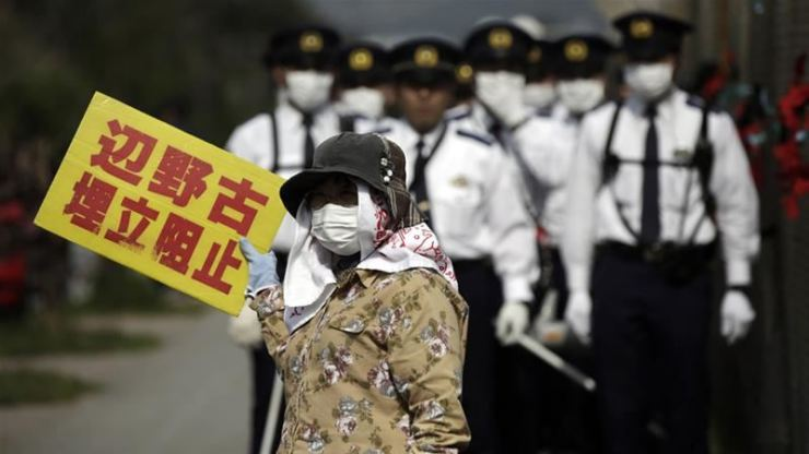 In this 2015 file photo, a masked protester displays a sign reading: 'Block reclamation of Henoko Beach.' AP