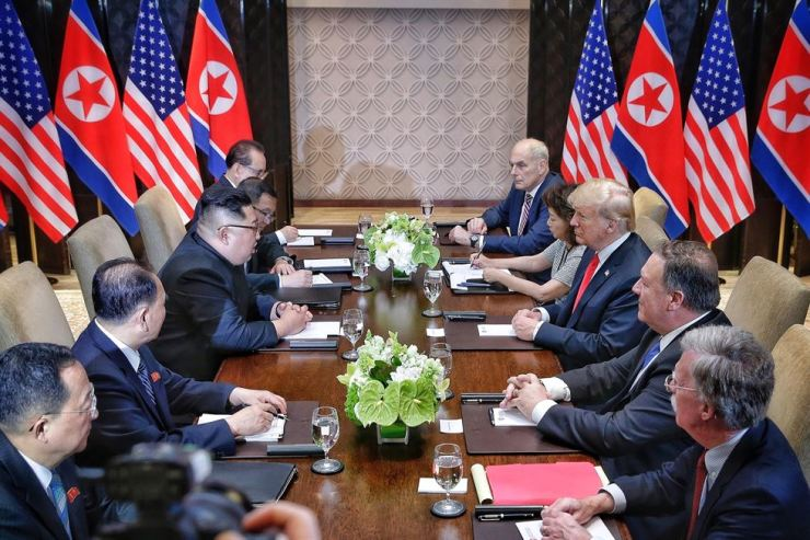 U.S. President Donald Trump and North Korean leader Kim Jong-un face each other during an extended meeting of their first summit in Singapore, June. The two are scheduled to meet for the second time in Vietnam later this month. Yonhap