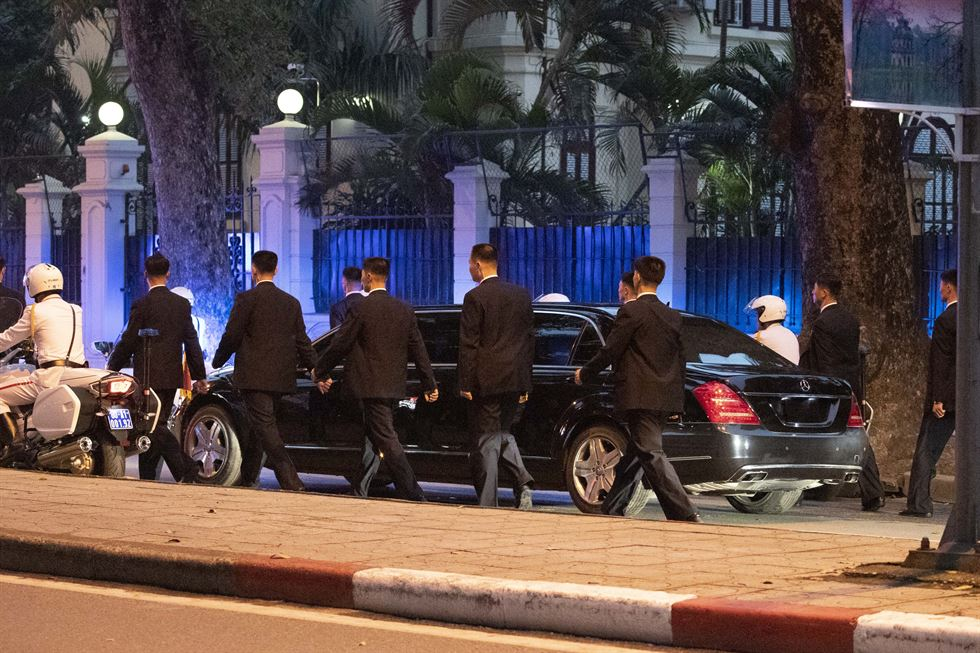 Bodyguards stand in protective formation around a Mercedes-Benz carrying North Korean leader Kim Jong-un, just before he gets out in front of the North Korean embassy building in Hanoi, Vietnam, Tuesday.  Korea Times photo by Choi Won-suk