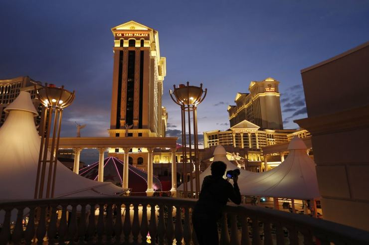 In this Monday, Jan. 12, 2015, file photo, a man takes pictures of Caesars Palace hotel and casino, in Las Vegas. AP