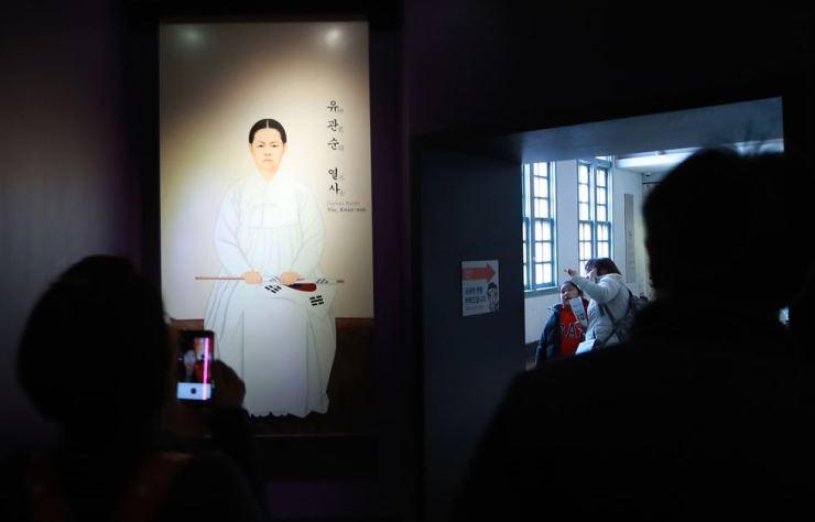 Visitors look at a portrait of Yu Gwan-sun at Seodaemun Prison History Hall in Seoul, Tuesday. Yonhap