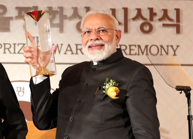 Indian Prime Minister Narendra Modi raises the Seoul Peace Prize trophy at Lotte Hotel in Seoul, Friday. Korea Times