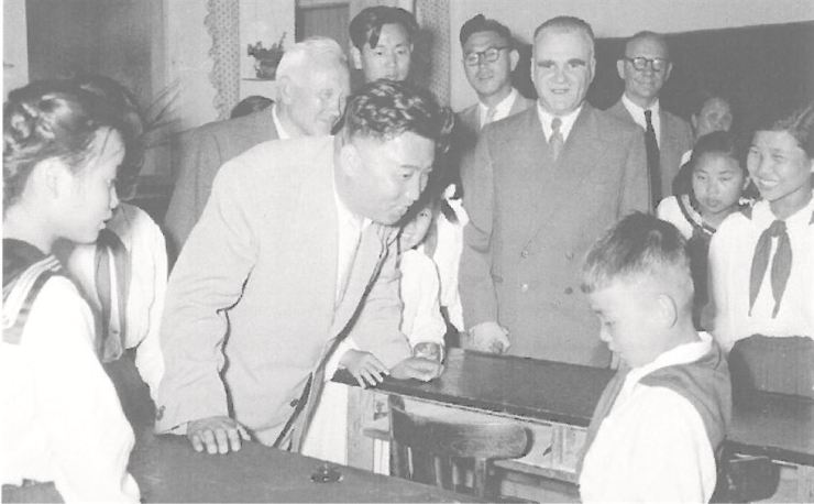 Then North Korean leader Kim Il-sung, center, the late grandfather of current leader Kim Jong-un, speaks to a Korean kid at an orphanage in Swider, 100 kilometers north of Warsaw, Poland, in this July, 1956 file photo. Kim paid a visit to the secluded Polish city on the sidelines of his state visit to Eastern Europe. The orphanage once housed 600 Korean War orphans until 1959 since the first batch of 200 Korean children arrived there Nov. 23, 1951. / Photo from Lee Hae-sung