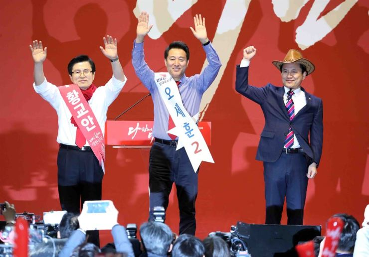 The main opposition Liberty Korea Party (LKP)'s leadership candidates, former Prime Minister Hwang Kyo-ahn, left, former Seoul Mayor Oh Se-hoon, center, and Rep. Kim Jin-tae wave during their first joint election campaign in Daejeon, Thursday. / Yonhap