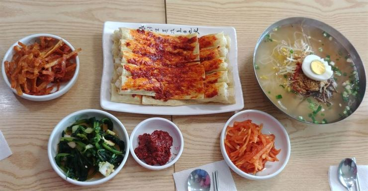Some of the food on offer at a Food North Korean restaurant named Howolilga in Incheon, Gyeonggi Province. In the center are injogogi rice roll with spices on the top. Injogi is fake or mock meat made from beans and sesame. On the right are hot noodles served with vegetables and spices. Korea Times photo by Jung Da-min