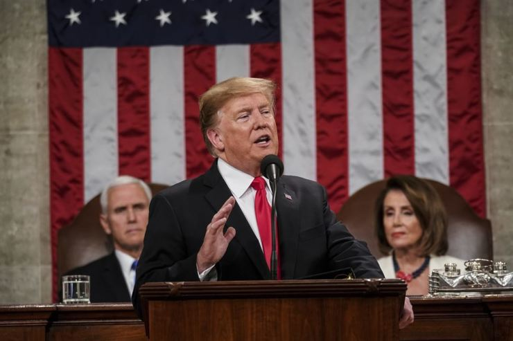 In this Feb. 5, 2019, photo, US President Donald Trump gives his State of the Union address to a joint session of Congress at the Capitol in Washington, as Vice President Mike Pence, left, and House Speaker Nancy Pelosi listen.