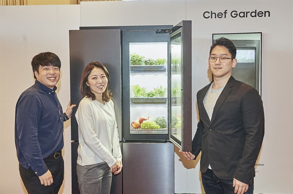 Samsung Electronics employees take a look at the Samsung Bot Chef robot during a showcase at the Encore at Wynn hotel in Las Vegas, Monday. / Courtesy of Samsung Electronics