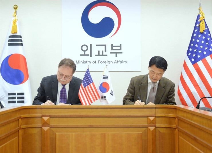 Timothy Betts, left, acting deputy assistant secretary and senior advisor for Security Negotiations and Agreements at the U.S. Department of State, and his South Korean counterpart Chang Won-sam sign a deal to raise South Korea's contribution to the upkeep of U.S. troops here, at the government complex in Seoul, Sunday. Yonhap