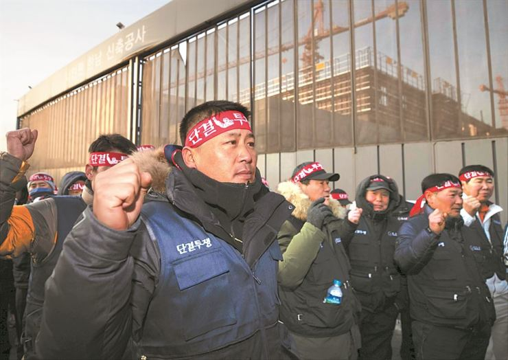 Members of the Korean Federation of Construction Industry Trade Unions stage a rally at a local construction site in Seoul, Monday, to call on the government to crack down on illegally employed migrant workers at construction sites. / Yonhap