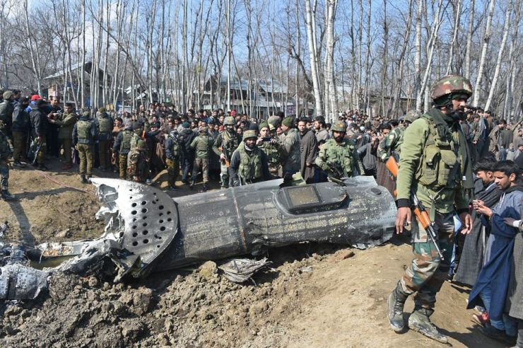 Indian soldiers and Kashmiri onlookers stand near the remains of an Indian Air Force helicopter after it crashed in Budgam district, outside Srinagar on February 27, 2019. - Officials said an investigation was underway into the cause of the crash, which came as Pakistan claimed to have shot down two Indian fighter jets in the divided and disputed Kashmir region. AFP