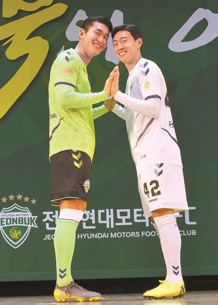Jeonbuk Motors' Lee Yong, left, and Han Seung-gyu reveal the new home and away uniforms, during the team's season opening ceremony at the North Jeolla Provincial Office in Jeonju, some 200 kilometers south of Seoul, Saturday. Courtesy of Jeonbuk Motors