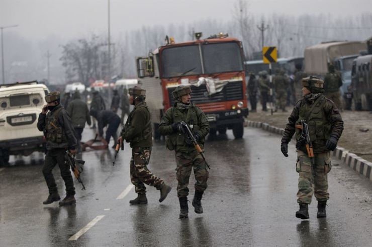 Indian paramilitary soldiers patrol at the site of an explosion in Pampore, Indian-controlled Kashmir, Feb. 14. Security officials say 37 soldiers have been killed and many others wounded by a large explosion that struck a paramilitary convoy on a key highway on the outskirts of the disputed region's main city of Srinagar. AP