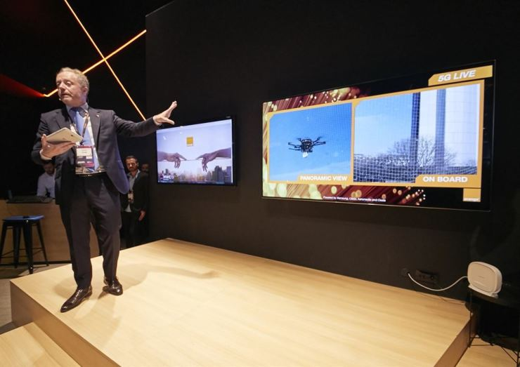A demonstrator in the Orange booth controls an outdoor drone remotely using a 5G tablet, which simultaneously displays a high-quality video feed captured by the drone and transmitted over a 5G network at the Mobile World Congress in Barcelona, Tuesday. / Courtesy of Samsung Electronics