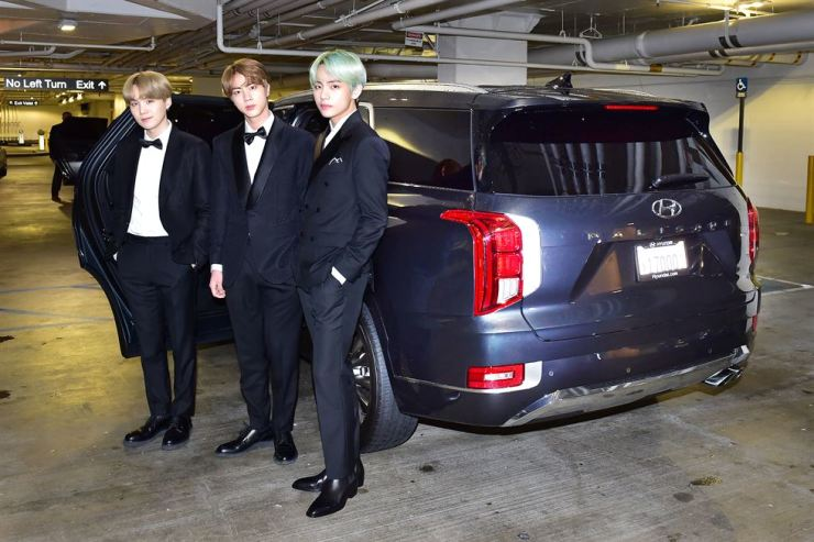 From left, boy group BTS members Suga, Jin and V, pose by a Hyundai Motor Palisade SUV at the InterContinental in Los Angeles before they attend the 61st Grammy Awards at The Staples Center, Monday. Hyundai Motor presented four Palisades to transport the K-pop sensation to the awards. BTS is the brand ambassador for the Palisade. Courtesy of Hyundai Motor