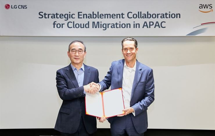 LG CNS CEO Kim Young-shub, left, poses with Ed Lenta, managing director of AWS in Asia-Pacific, after signing an agreement to co-develop a cloud computing program for local firms at the LG Science Park in Seoul, Friday. / Courtesy of LG CNS