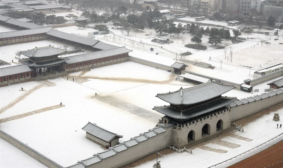 Two workers clear snow at the National Assembly, Friday. More snow fell in the afternoon. Yonhap