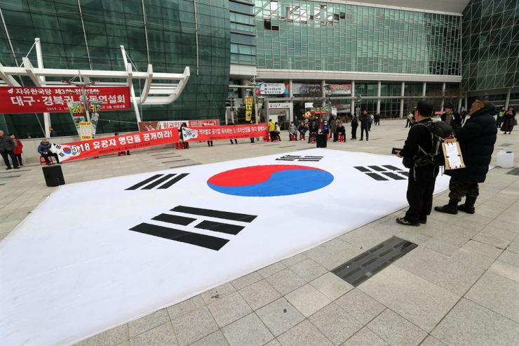 A national flag is on the ground near Exco, Daegu, Monday, before the main opposition Liberty Korea Party (LKP) holds its joint speech session there for candidates of its leadership race on Feb. 27. / Yonhap
