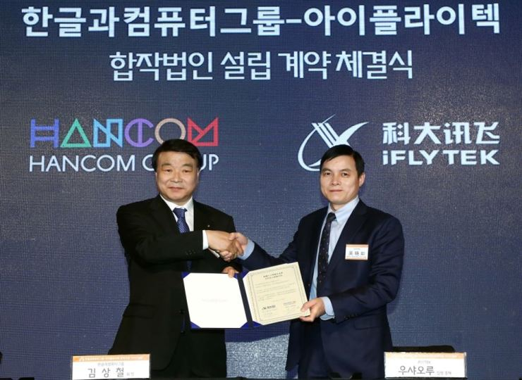 Hancom Group Chairman Kim Sang-chul, left, shakes hands with iFLYTEK Group Executive President Wu Xiaoru after signing a contract to set up a joint venture on AI business at the Four Seasons Hotel in Gwanghwamun, central Seoul, Wednesday. / Courtesy of Hancom Group