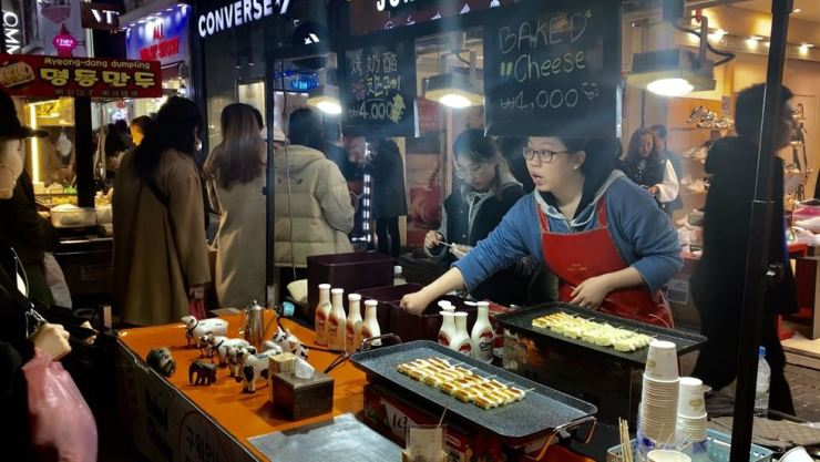 A vendor makes grilled cheese and skewered rice cakes. Myeong-dong is a cultural melting pot where various creative cross-cultural fusion foods are pushing aside the homegrown street food trio ― gimbap, tteokbokki and sundae. Korea Times photo by Lee Han-na