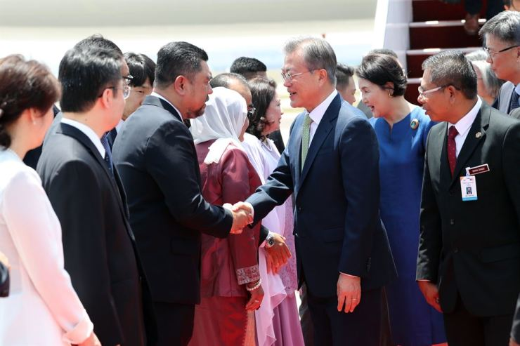 President Moon Jae-in, center, shakes hands with Malaysian officials at the Kuala Lumpur International Airport, Malaysia, Tuesday. Moon is on a three-nation state visit to Brunei, Malaysia and Cambodia in a move to boost ties with the ASEAN countries. / Yonhap