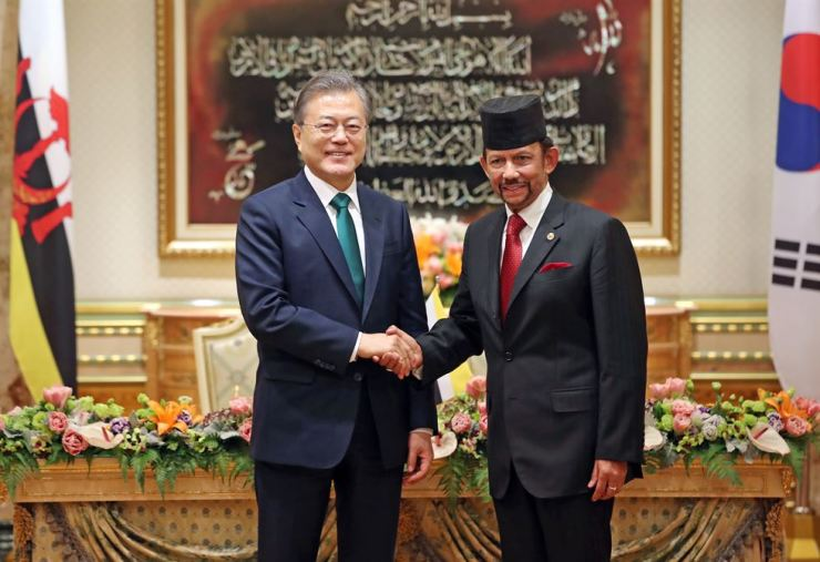 President Moon Jae-in, left, shakes hands with Brunei's monarch Sultan Hassanal Bolkiah at the start of their summit in the Sultan's palace in Bandar Seri Begawan, Monday. Yonhap
